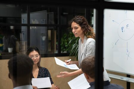 Photo for Young confident female team leader giving out paper economic growth reports to focused motivated millennial mixed race colleagues. Multiracial team working together, discussing project on meeting. - Royalty Free Image