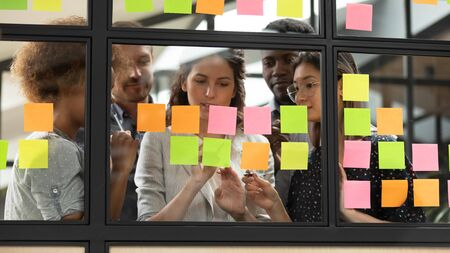 Foto de Focused young diverse teammates working with caucasian team leader on IT startup project kanban organization process, discussing details and tasks, writing notes on colorful paper stickers at office. - Imagen libre de derechos