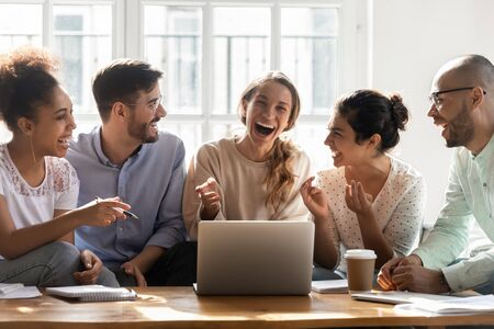Photo pour Happy young friends watching overjoyed mixed race girl laughing at joke, watching funny videos together. Positive diverse people having fun, meeting together for college project discussion at home. - image libre de droit