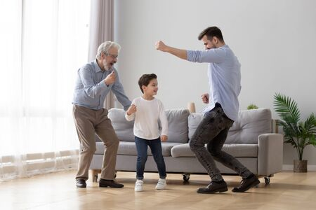 Foto de Happy grandfather, father and little son having fun at home, excited granddad, dad and preschool child boy grandchild dancing to favorite music together, family playing in living room, funny activity - Imagen libre de derechos