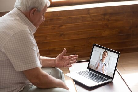 Foto de Focused older 80s male patient consulting with doctor via computer video call. Senior man looking at laptop screen, talking to therapist cardiologist online, older generation using modern technology. - Imagen libre de derechos