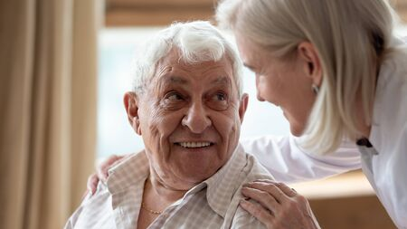 Photo pour Head shot close up cheerful elderly man looking at pleasant middle aged nurse. Mature female doctor embracing shoulders, communicating with smiling 80s patient, giving support and psychological help. - image libre de droit