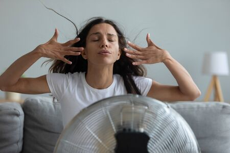 Foto de Woman seated on couch in living room suffers from swelter waving her hands trying to cool off by the fan, oppressive heat too hot weather and sultriness in summer, flat without air-conditioner concept - Imagen libre de derechos