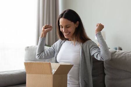 Foto de Cheery woman sitting on couch opening cardboard box feeling excitement and happiness girl received long-awaited carton package, fast post mail parcel delivery, reliable postal courier service concept - Imagen libre de derechos