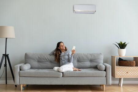 Photo pour Woman spend time at home seated on sofa holding remote control manages degrees uses air conditioner enjoy air-conditioned contemporary flat, reduces heat or cold weather to comfortable temperature - image libre de droit