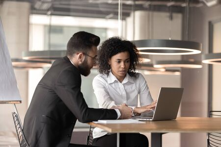 Foto de Concentrated multiracial businesspeople sit in office using computer discuss project together, focused diverse multiethnic man and woman employees or partners work on laptop cooperating at meeting - Imagen libre de derechos