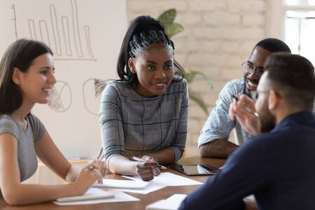 Photo for Positive successful mixed race group of managers working together at office, sharing project ideas, writing down notes, preparing financial documentation, developing marketing strategy together. - Royalty Free Image