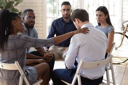 Foto de Compassionate african american female employee putting hand on desperate coworkers shoulder, supporting, expressing condolence. Mixed race diverse team of workers sitting in circle on group therapy. - Imagen libre de derechos