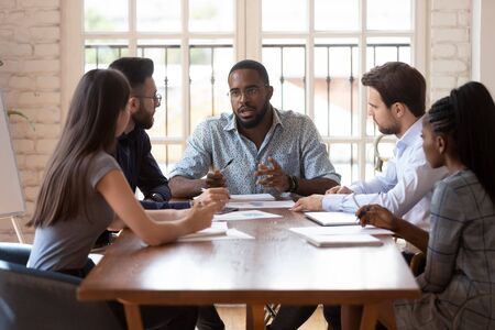Photo for Diverse group of professionals sitting at table at brainstorming meeting, listening to african american confident male team leader, explaining planning company marketing developing strategy at office. - Royalty Free Image