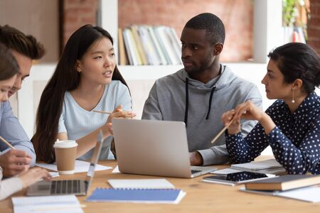 Photo pour Focused young indian girl and black guy listening to groupmate. Asian female student explaining school project details or sharing ideas with college friends. Group of diverse teens working together. - image libre de droit