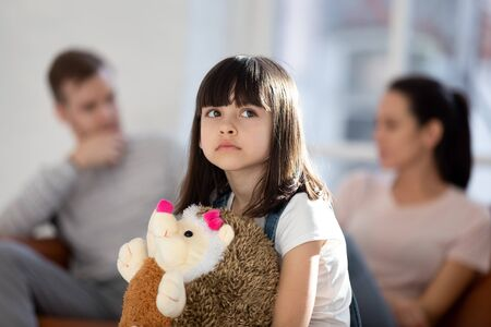 Foto de Sad little girl feel upset lonely hug fluffy toy hedgehog friend affected by parent fight or quarrel, upset small child loner stressed with mom and dad divorce or split, family problems concept - Imagen libre de derechos