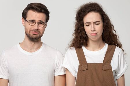 Foto de Sad millennial couple isolated on grey studio background feel unhappy depressed crying having life problems, distressed down young man and woman lost in despair mourn suffer from troubles - Imagen libre de derechos