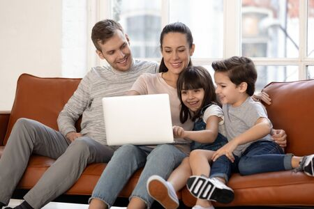 Photo pour Happy young family with cute preschooler kids have fun at home watching movie on laptop together, loving parents and little children relax in living room smile enjoying cartoon on computer - image libre de droit