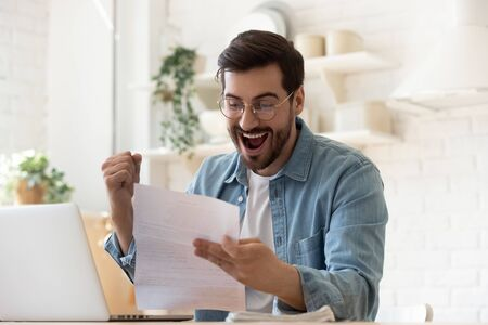Foto de Excited euphoric happy young man holding reading paper postal mail letter amazed overjoyed by good news, got new job celebrate taxes refund receive salary payment loan approval sit at home table - Imagen libre de derechos