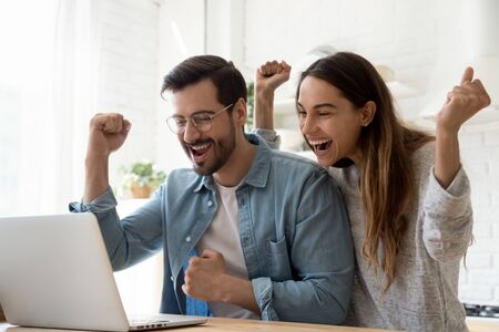 Foto de Excited overjoyed young family couple winners feel lucky got sale discount offer by email look at laptop screen celebrate online victory internet auction bid lottery win in app computer technology - Imagen libre de derechos