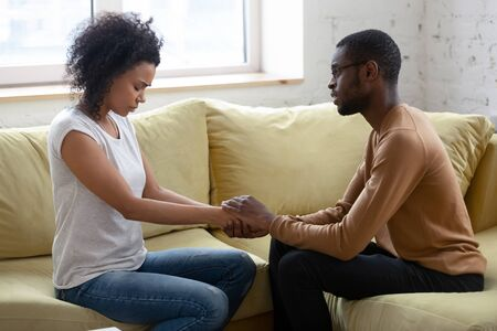 Photo for Loving african American husband hold beloved wife hands caressing make peace after family fight or misunderstanding, caring biracial man comfort support sad depressed woman, asking forgiveness - Royalty Free Image