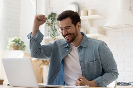 Foto de Excited young man winner sit at home table looking at laptop screen celebrating online success victory euphoric overjoyed by internet sport bet win got new job opportunity or loan approval in email - Imagen libre de derechos