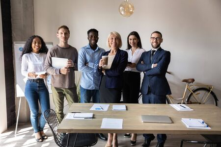 Photo for Positive middle aged female team leader posing in office with happy successful mixed race young teammates. Portrait of skilled professional international group of diverse experts, looking at camera. - Royalty Free Image