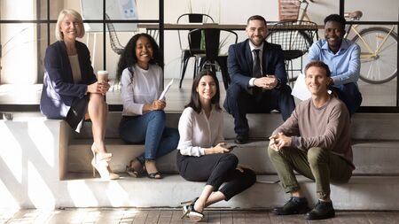 Photo for Portrait of happy middle aged and young coworkers sitting on stairs in modern office. Positive different generations mixed race business people enjoying informal communication in loft workplace. - Royalty Free Image