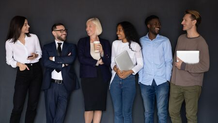 Photo for Group of successful happy diverse young and older business people staff with gadgets standing in line near black wall, communicating, talking, having fun together, human resource team concept. - Royalty Free Image