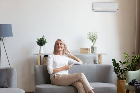 Foto de 50s woman rest on couch closed eyes enjoy fresh air hold remote control use air conditioner cools herself at summer hot day adjusting temperature inside of living room, comfort wellbeing life concept - Imagen libre de derechos