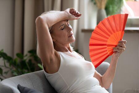 Foto de Middle-aged woman leaned on sofa resting in living room cools herself with orange colour hand fan touch forehead feels unwell suffers from unbearable hot summer weather at home without airconditioner - Imagen libre de derechos