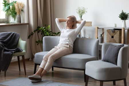 Photo for Attractive elderly woman resting on couch putting hands behind head enjoy fresh air spend weekend free time in modern cozy living room. Concept of no stress, calm retired life, take break, keep calm - Royalty Free Image