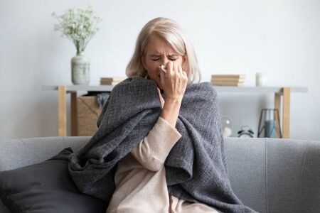 Foto de Middle-aged 50s sick frozen woman seated on sofa in living room covered with warm plaid sneezing holding paper napkin blow out runny nose feels unhealthy, seasonal cold, weakened immune system concept - Imagen libre de derechos
