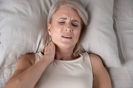 Photo pour Top close up view middle-aged woman lying in bed in morning feels pain in neck after night sleep, awaken having painful sudden ache or stiffness, incorrect posture during asleep, soft mattress concept - image libre de droit