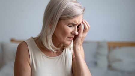 Photo pour Close up of tired middle-aged woman touches face with hand having migraine or depression, frustrated old female troubled with personal or health problem feels stressed crying suffer from grief concept - image libre de droit