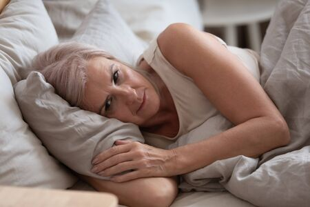 Foto de Close up view sleepless middle-aged woman lying in bed suffers from insomnia sleep disorder cant sleep till morning, depressed elderly female looking upset thinking about life, health troubles concept - Imagen libre de derechos