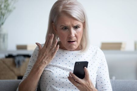 Foto de Elderly 50s woman sitting on couch in living room holding smart phone gesturing looking annoyed feels angry having problem with gadget, slow internet, connection lost, discharged broken device concept - Imagen libre de derechos