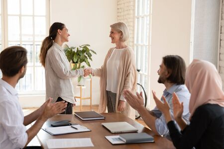 Photo pour Satisfied with good job results smiling older team leader shaking hands with happy female colleague while diverse teammates clapping hands. Smiling boss praising coworker at business meeting. - image libre de droit