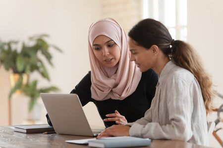 Photo pour Concentrated young arabian woman in hijab sitting with smiling colleague at table, looking at computer screen, explaining new company software. Focused team leader training millennial female intern. - image libre de droit