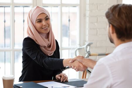 Foto de Pleasant smiling arabian female hr manager in hijab shaking hands with male job applicant. Young happy arabic businesswoman welcoming partner or making agreement with client at meeting in office. - Imagen libre de derechos