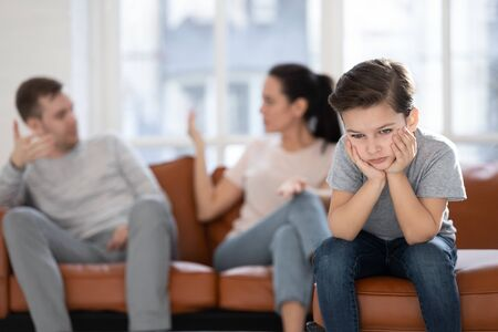 Photo pour Close up little boy suffering from parents conflict sitting at couch. Sad son frustrating hear mother and father fighting arguing and bad situation, family conflict, divorce. - image libre de droit