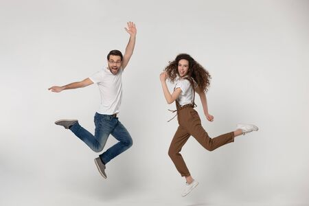 Photo for Joyful young man and happy millennial girl jumping high with raised hands and bent in knees legs, flying, having fun during photo shooting process near softbox light, isolated grey background. - Royalty Free Image