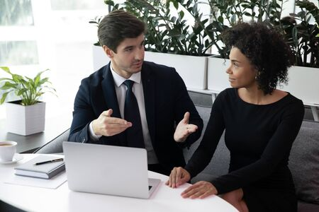 Photo for Focused young businessman in suit communicating with motivated african american female colleague in office. Pleasant biracial businesswoman listening to partners propose at brainstorming meeting. - Royalty Free Image