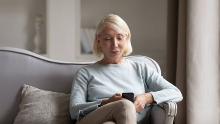Photo pour Smiling mature woman sit on couch using new smartphone browsing fast wireless unlimited internet on gadget, happy modern middle-aged female relax at home surfing web on cellphone device - image libre de droit
