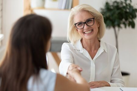 Photo for Smiling middle-aged businesswoman shake hand get acquainted greeting with female applicant, happy senior woman boss handshake candidate or business partner after successful interview or meeting - Royalty Free Image