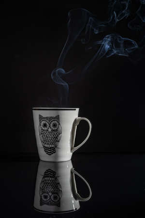 Foto de Coffee cup with its reflection with black background. Smoke comes out of the mug. The mug has the image of an owl - Imagen libre de derechos