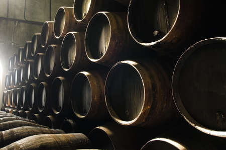 Photo pour Barrels for whiskey or wine stacked in the cellar - image libre de droit