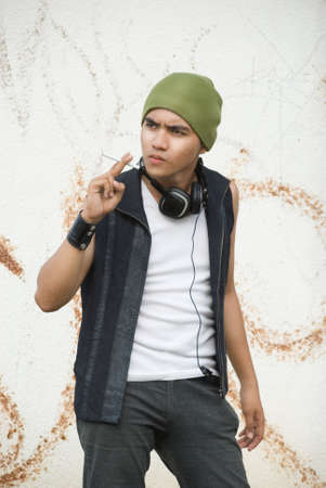 Young Hispanic rapper dude in urban casual grunge clothing or funky fashion with cap, headphones and cigarette hanging out against background of graffiti wall.