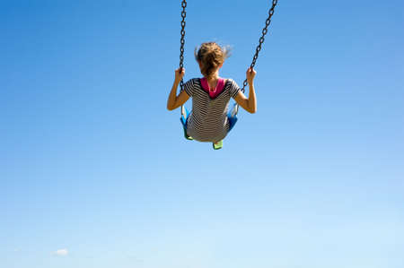 A young girl playing on a swingset in front of a blue sky.  Girl is swinging very high in swing, with copy space