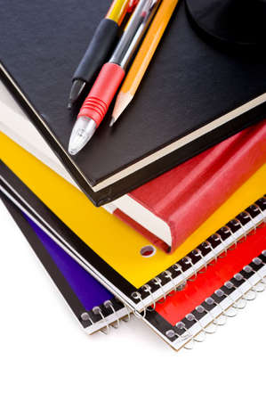 A stack of school books and spiral notebooks with a pencil and pens on tops in front of a white background