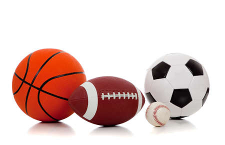 An assortment of sports balls including basketball, american football, soccerball and baseball on a white background
