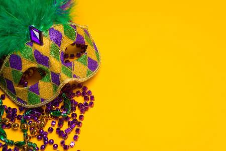 Foto de A festive, colorful mardi gras or carnivale mask on a yellow background   Venetian mask  - Imagen libre de derechos