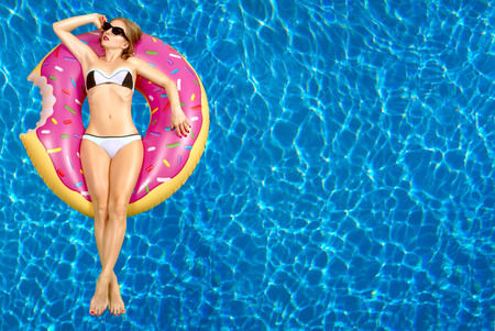 Photo for Summer Vacation. Enjoying suntan Woman in bikini on the inflatable mattress in the swimming pool. - Royalty Free Image