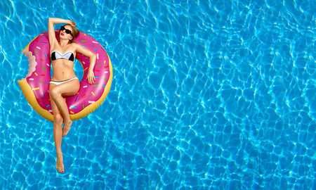 Foto de Summer Vacation. Enjoying suntan Woman in bikini on the inflatable mattress in the swimming pool. - Imagen libre de derechos