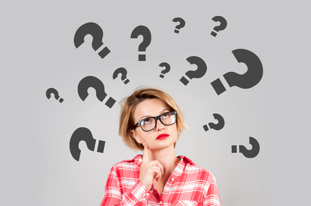 Photo pour Thinking woman with questioning expression and question marks above her head - image libre de droit
